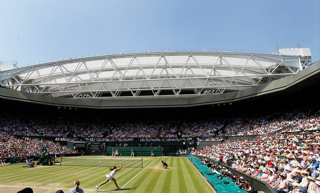 Description of . Marion Bartoli of France, foreground, plays a return to Sabine Lisicki of Germany during their Women's singles final match at the All England Lawn Tennis Championships in Wimbledon, London, Saturday, July 6, 2013. (AP Photo/Kirsty Wigglesworth)
