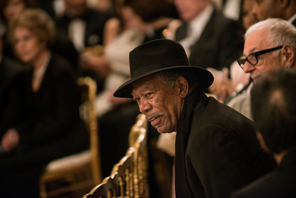Description of . Actor Morgan Freeman listens during an event in the East Room of the White House December 2, 2012 in Washington, DC. Obama and US First Lady Michelle Obama attended the event at the White House with the 2012 Kennedy Center Honorees before to celebrate their contribution to the arts before heading to the Kennedy Center for the honors program. BRENDAN SMIALOWSKI/AFP/Getty Images