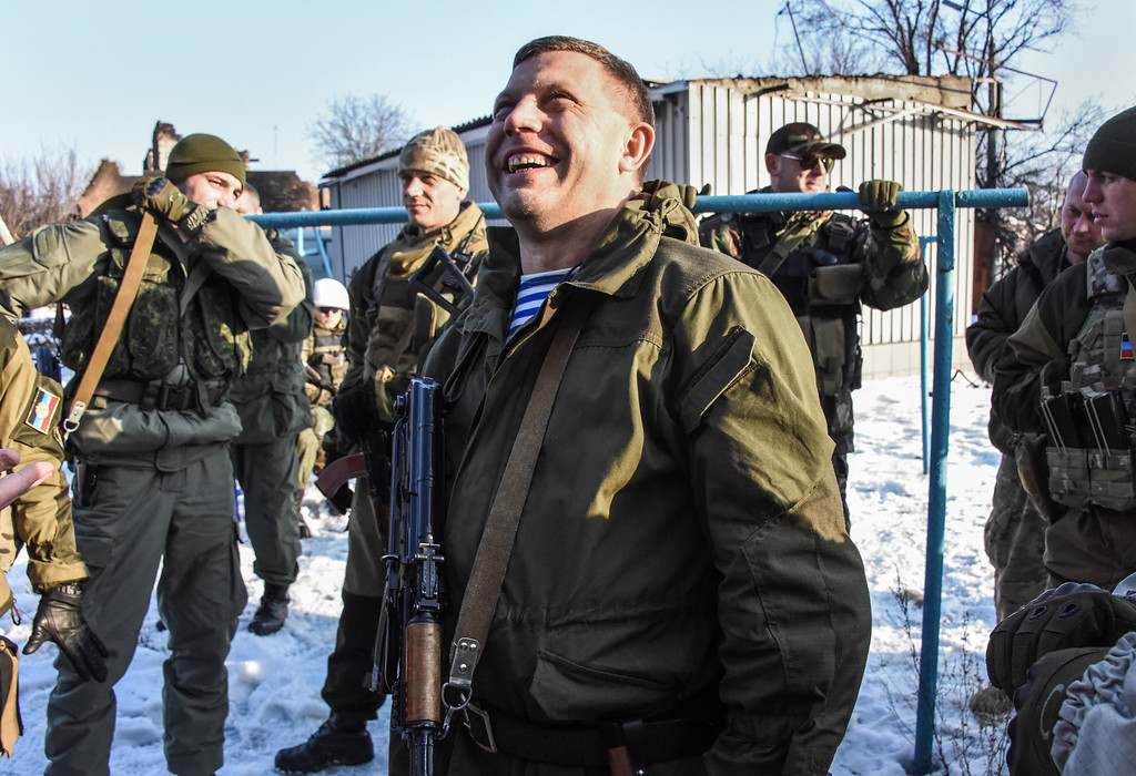 Description of . In this Thursday, Jan. 15, 2015 photo, Pro-Russian rebel leader Alexander Zakharchenko, center, surrounded by guards, smiles not far from rebel positions near the Donetsk airport in Donetsk, Eastern Ukraine. Russian-backed separatists announced Thursday they had captured the shattered remains of the Donetsk airport terminal and plan to claw back more territory, further dashing hopes for a lasting peace agreement. (AP Photo/Mstyslav Chernov)