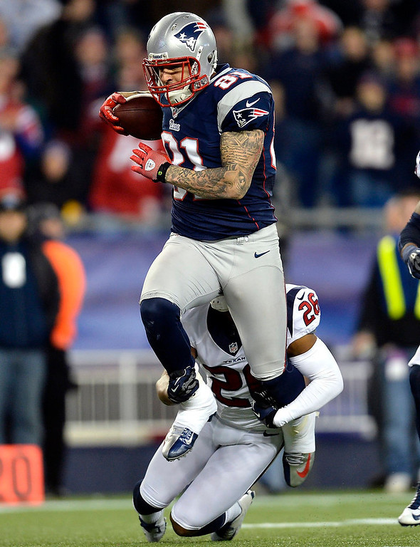 Description of . New England Patriots tight end Aaron Hernandez (81) runs for a long gain deep into Houston Texans territory after catching a pass from quarterback Tom Brady during the third quarter of their NFL AFC Divisional playoff football game in Foxborough, Massachusetts January 13, 2013. The tackle is being made by Texans\' Brandon Harris.  REUTERS/Gretchen Ertl