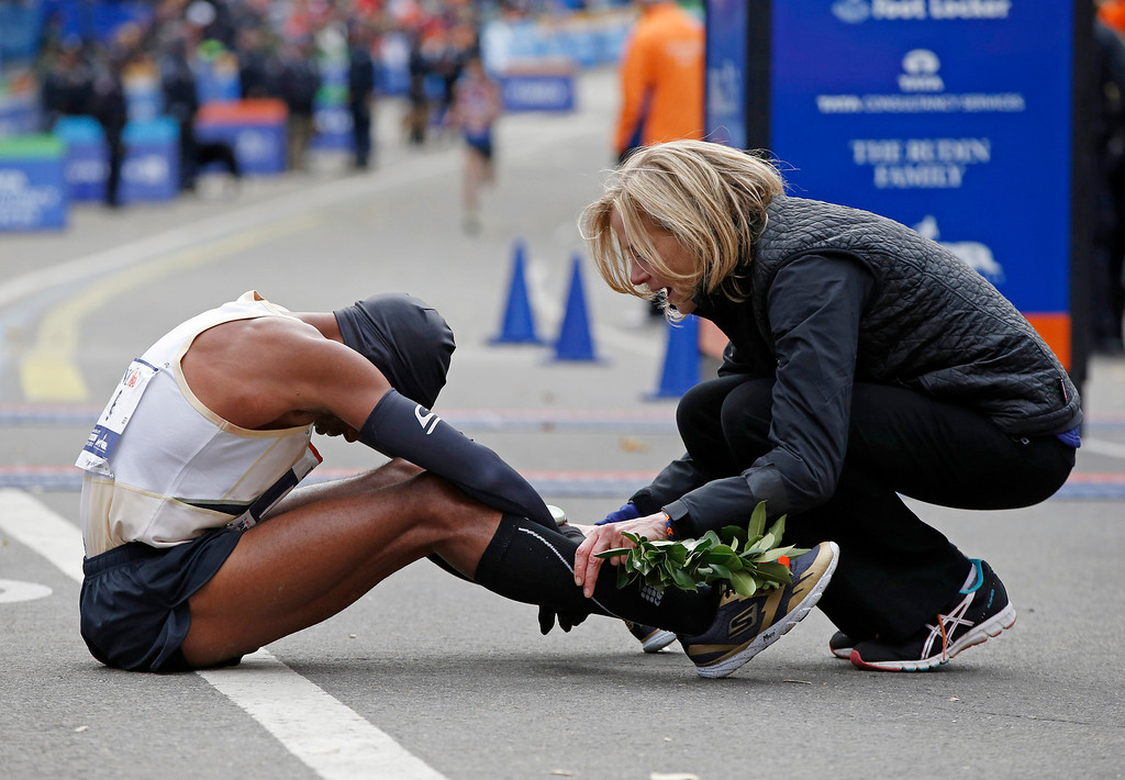 Description of . New York Road Runners president Mary Wittenberg consoles Meb Keflezighi of California at the finish line of the New York City Marathon, Sunday, Nov. 3, 2013, in New York.  (AP Photo/Kathy Willens)