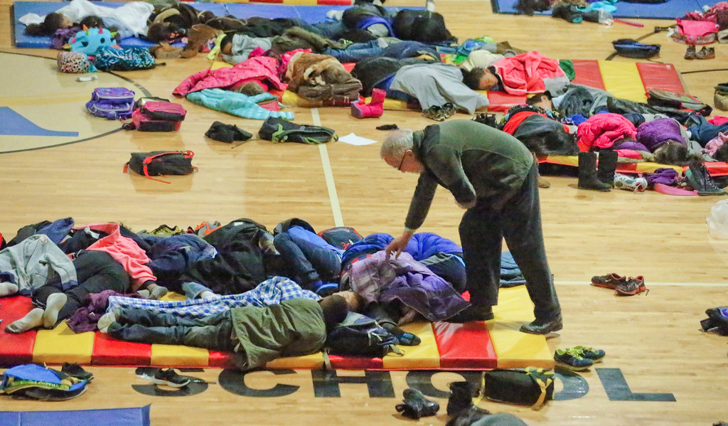 Description of . A teacher at E. Rivers Elementary school covers sleeping children in the gymnasium of the school who were forced to stay in the aftermath of a winter storm in Atlanta, Georgia, USA, 29 January 2013. 115 students and 35 staff members including some parents and bus drivers spent the night at the school. Two movies with popcorn were served after a pizza dinner from the cafeteria. Thousands of commuters and students were unable to reach their homes in the aftermath of the storm.  EPA/JOHN SPINK / ATLANTA JOURNAL CONSTITUTION