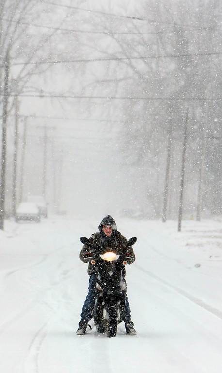Description of . Jesse Ray, 16, rides his moped to a friend's house on Friday, Dec. 6, 2013, in Owensboro, Ky. A wintry mix struck the western part of Kentucky first but was moving eastward by Friday afternoon, and much of the eastern half of the U.S. was blanketed in precipitation. (AP Photo/The Messenger-Inquirer, John Dunham)