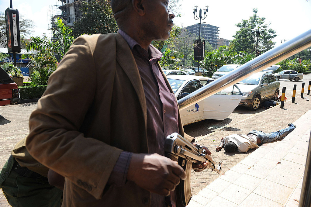 Description of . A body of a man lies on the ground as armed policemen try to get entry into the Westgate after masked gunmen stormed an upmarket mall and sprayed gunfire on shoppers and staff, killing at least six on September 21, 2013 in Nairobi. The Gunmen have taken at least seven hostages, police and security guards told an AFP reporter at the scene. AFP PHOTO/SIMON MAINA/AFP/Getty Images