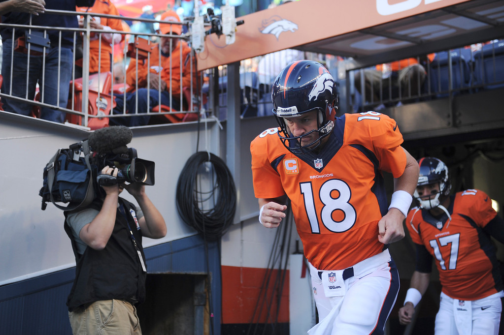 Description of . Denver Broncos quarterback Peyton Manning (18) runs onto the field for warm-ups before the start of the game. The Denver Broncos took on the Oakland Raiders at Sports Authority Field at Mile High in Denver on September 23, 2013. (Photo by Joe Amon/The Denver Post)
