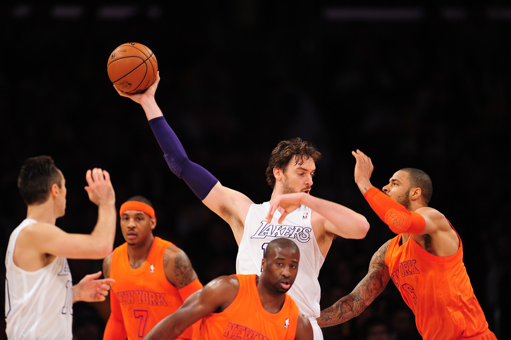 Description of . Pau Gasol (C)of the Los Angeles Lakers grabs the ball against the New York Knicks during their NBA game at Staples Center in Los Angeles, California, on December 25, 2012.  ROBYN BECK/AFP/Getty Images