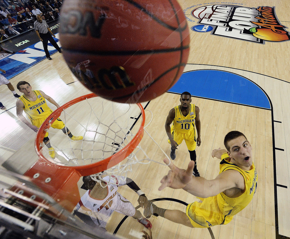 Description of . Michigan forward Mitch McGary (4) lays up the ball against the Louisville during the first half of the NCAA Final Four tournament college basketball championship game Monday, April 8, 2013, in Atlanta. (AP Photo/NCAA Photos, Chris Steppig)