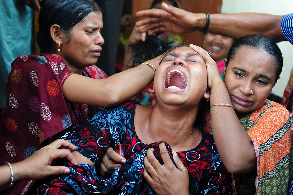 Description of . Relatives react after identifying the body of a loved one killed in a building collapse in Savar, on the outskirts of Dhaka, on May 3, 2013. The death toll passed 500 as the country's prime minister said Western retailers had to share some of the blame for the tragedy.  MUNIR UZ ZAMAN/AFP/Getty Images