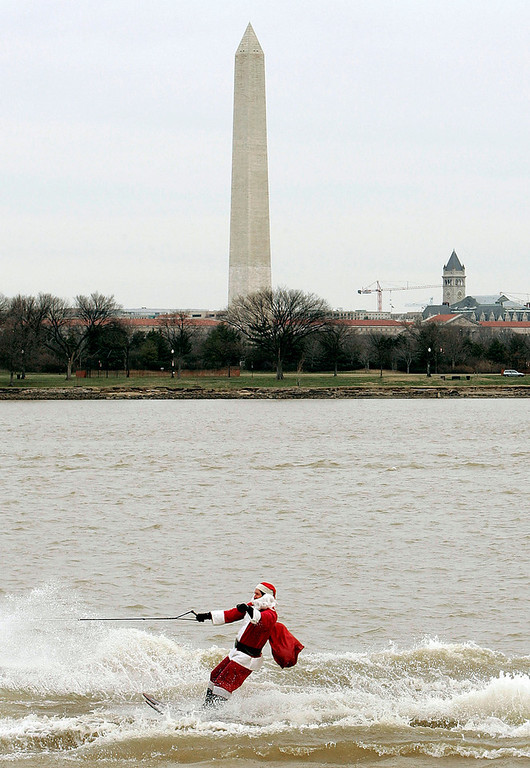 Description of . Dressed as Santa Claus, Kerry Nistel water-skis past the Washington Monument on the frigid waters of the Potomac River December 24, 2004 in Arlington, Virginia. This is the 19th year Nistel has dressed as Santa and water-skied on Christmas Eve.  (Photo by Mark Wilson/Getty Images)