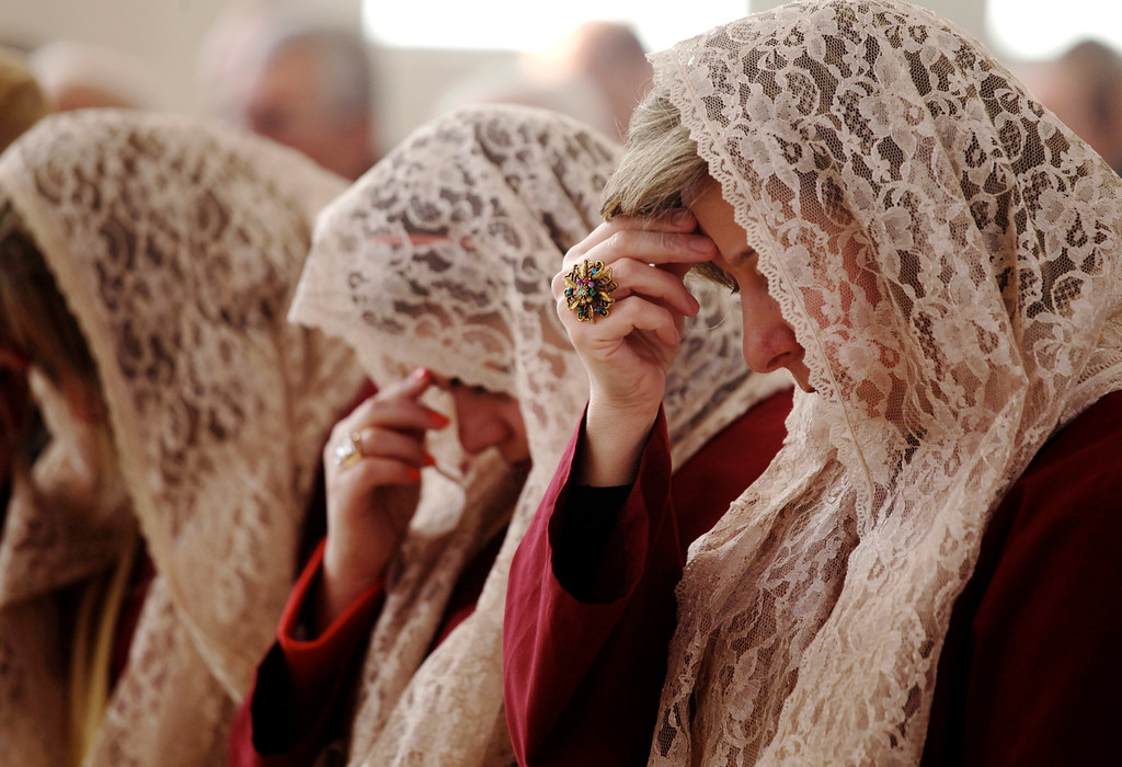 Description of . The women of Saint Afram Syrian Orthodox church's choir pray during morning Christmas mass in Amman, Jordan, Wednesday, Dec. 25, 2013. Syrian and Iraqi Orthodox Christian families prayed for peace in their countries. (AP Photo/Mohammad Hannon)