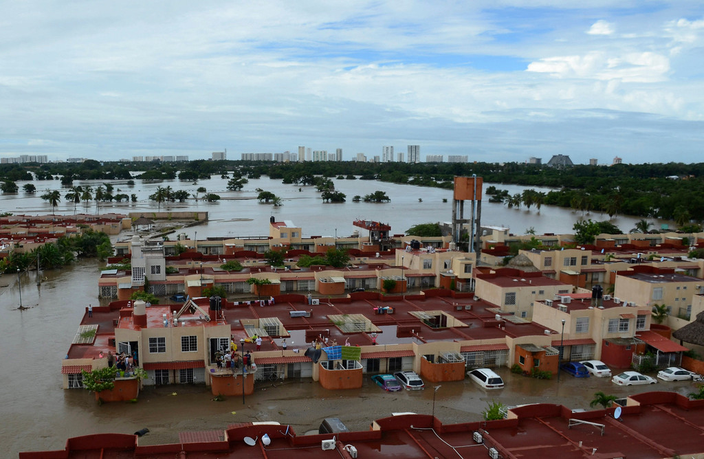 Description of . People stand on the rooftop of a home in a flooded neighborhood after Tropical Storm Manuel pounded Acapulco, Mexico, Tuesday, Sept. 17, 2013. The death toll rose to 47 Tuesday from the unusual one-two punch of a tropical storm and a hurricane, hitting Mexico at nearly the same time. Authorities scrambled to get help into, and stranded tourists out of, the cutoff resort city. (AP Photo/Bernandino Hernandez)