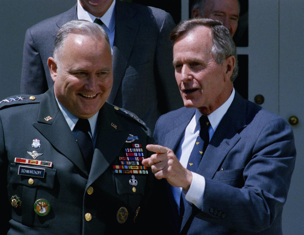 Description of . President Bush gestures while posing for photographer with Gen. Norman Schwarzkopf in the White House Rose Garden, April 23, 1991 in Washington. Schwarzkopf, just back from commanding the U.S.-led military victory over Iraq, joined the President for lunch at the White House. (AP Photo/Marcy Nighswander)