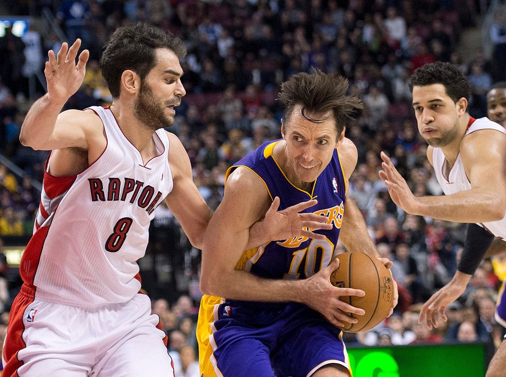 Description of . Los Angeles Lakers guard Steve Nash, center, drives past Toronto Raptors guard Jose Calderon, left, and forward Landry Fields, right, during the second half of an NBA basketball game in Toronto on Sunday, Jan. 20, 2013. (AP Photo/The Canadian Press, Nathan Denette)
