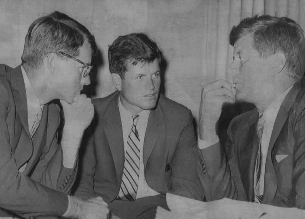 Description of . Robert F. Kennedy, left, then counsel for the Senate Rackets Committee, is shown during a committee hearing in  1959 in Washington conferring with his brothers, Sen. John F. Kennedy, right, and Edward Kennedy, center.