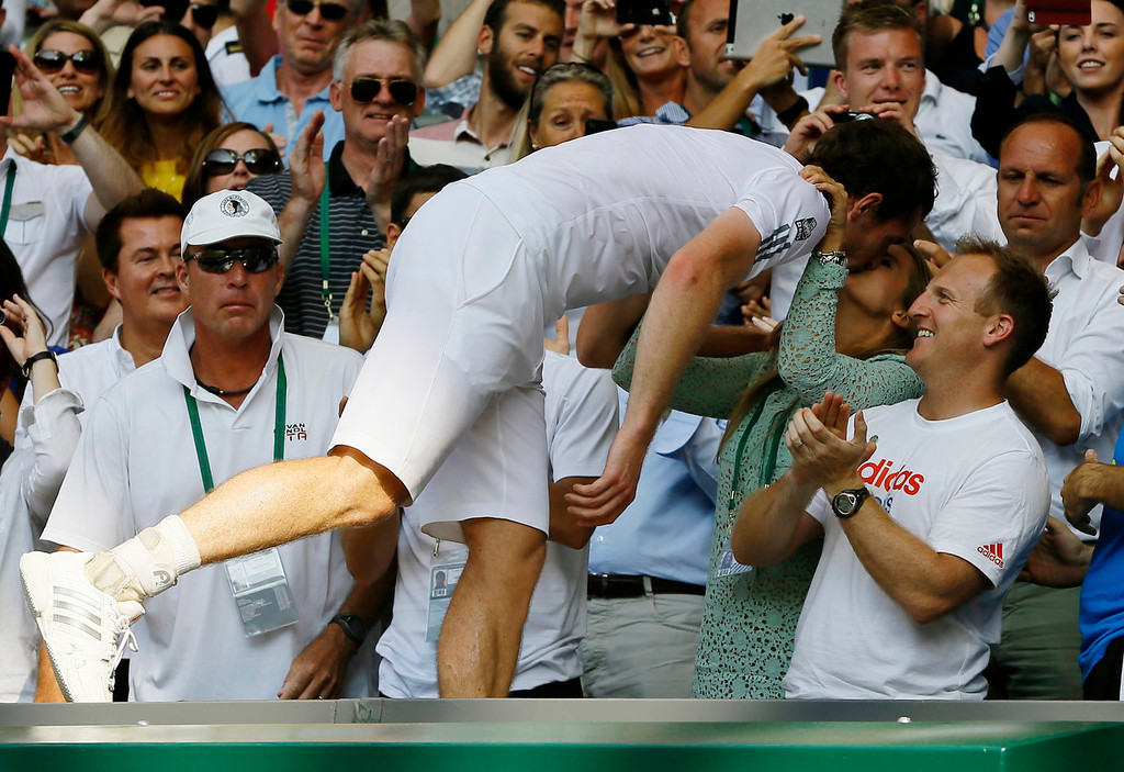 Description of . Andy Murray of Britain, center, kisses his girlfriend Kim Sears after defeating Novak Djokovic of Serbia during the Men's singles final match at the All England Lawn Tennis Championships in Wimbledon, London, Sunday, July 7, 2013. (AP Photo/Kirsty Wigglesworth)