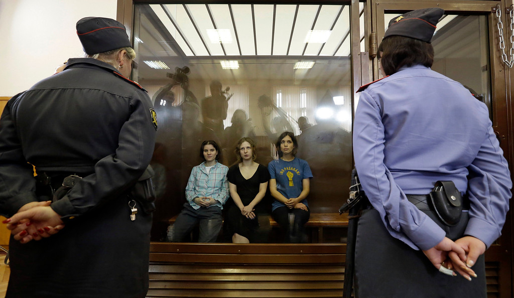 Description of . In this Aug. 17, 2012 file photo, feminist punk group Pussy Riot members, from left, Yekaterina Samutsevich, Maria Alekhina and Nadezhda Tolokonnikova sit in a glass cage at a court room in Moscow, Russia. The women, two of whom have young children, are charged with hooliganism connected to religious hatred. The case was widely seen as a warning that authorities will tolerate opposition only under tightly controlled conditions. T-shirt on right worn by Tolokonnikova is Spanish and translates to