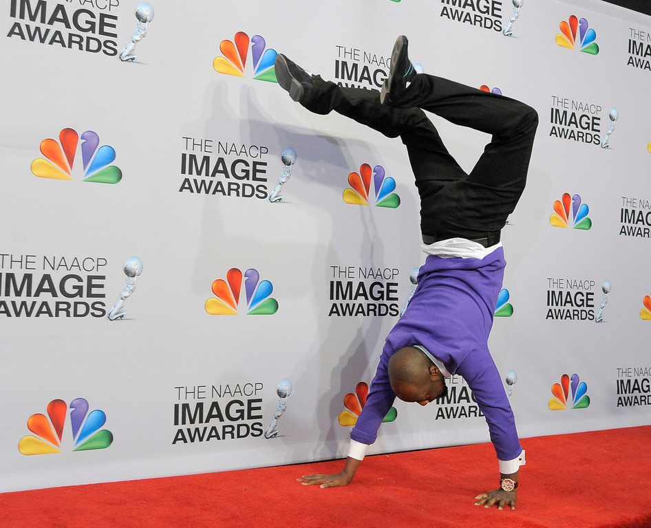 Description of . Wyclef Jean does a handstand backstage at the 44th Annual NAACP Image Awards at the Shrine Auditorium in Los Angeles on Friday, Feb. 1, 2013. (Photo by Chris Pizzello/Invision/AP)