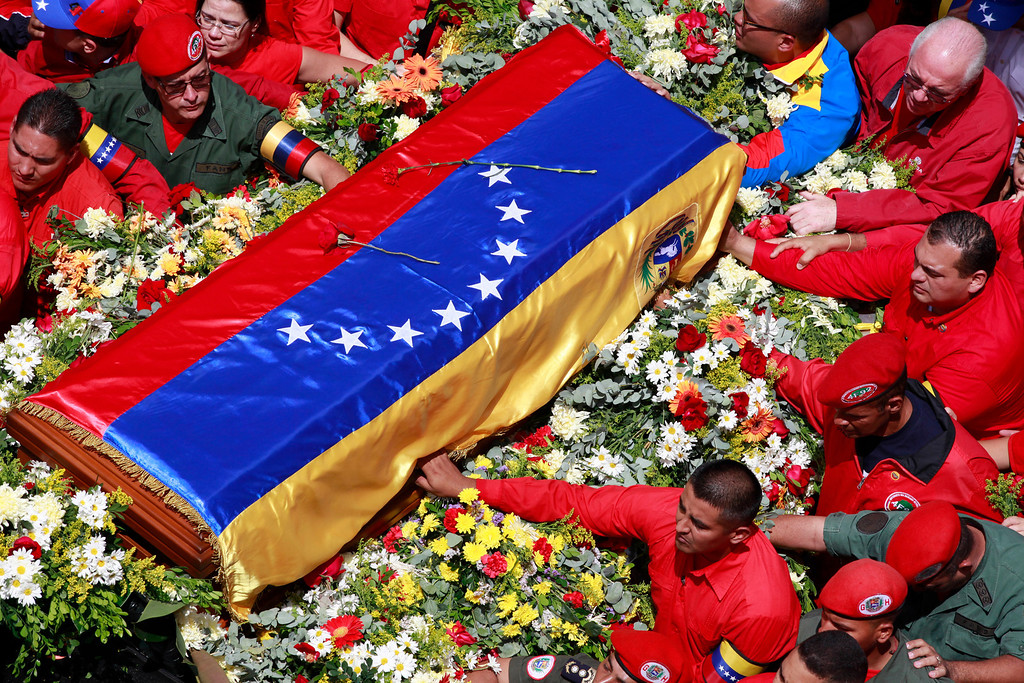Description of . The flag-draped coffin containing the body of Venezuela's late President Hugo Chavez is taken from the hospital where he died, to a military academy, where it will remain until his funeral in Caracas, Venezuela, Wednesday, March 6, 2013. Seven days of mourning were declared, all schools were suspended for the week and friendly heads of state were expected for an elaborate funeral. (AP Photo/Ricardo Mazalan, File)