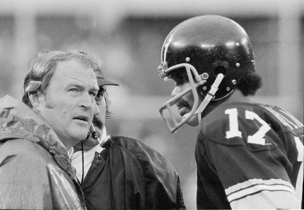Description of . Pittsburgh Steelers head coach Chuck Noll, left, with Terry Hanratty at his side, looks at the clock as he talks with quarterback Joe Gilliam during their 17-0 loss to the Oakland Raiders in Pittsburgh Sunday, Sept. 30, 1974. (AP Photo/Harry Cabluck)