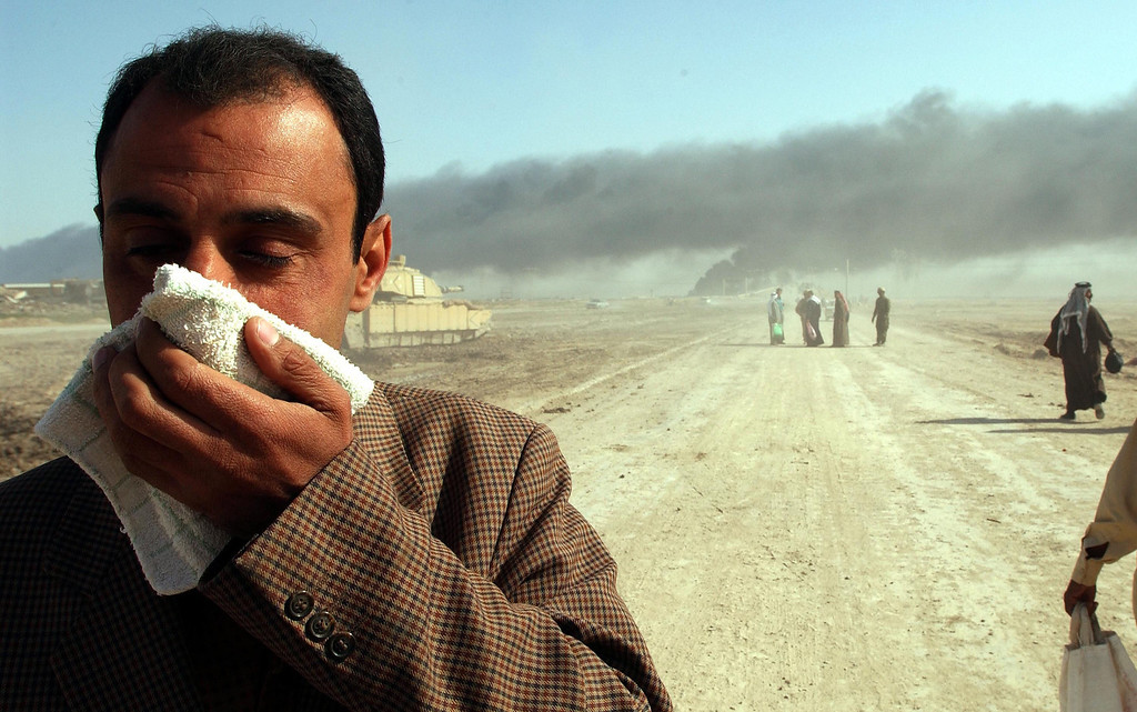 Description of . As oil fires burn in the distance, a man covers his face near the entrance to the besieged city of Basra on March 29, 2003 in Iraq. Baath Party loyalists took up positions in Basra, Iraq\'s second largest city, making it a target of the U.S.-led war on Iraq. (Photo by Spencer Platt/Getty Images)