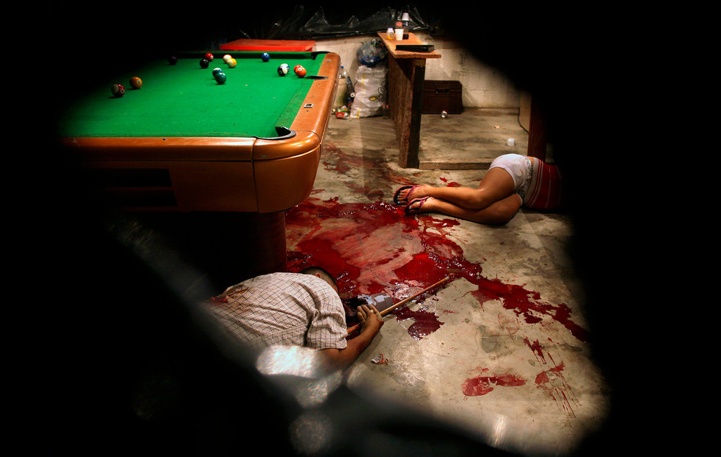 Description of . In this March 11, 2012 file photo, the bodies of Lesbia Altamirano and Wilmer Orbera lie on the floor of a pool hall after being attacked by unidentified masked assailants in Choloma on the outskirts of San Pedro Sula, Honduras. This photo by Associated Press photographer Esteban Felix won the second place prize for the Contemporary Issues singles category in the World Press Photo 2013 photo contest. (AP Photo/Esteban Felix, File)