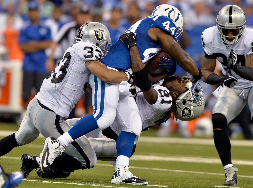 Description of . Indianapolis Colts running back Ahmad Bradshaw (44) knock the helmet off of Oakland Raiders cornerback Mike Jenkins (21) as Bradshaw is tackled by strong safety Tyvon Branch during the second half of an NFL football game in Indianapolis, Sunday, Sept. 8, 2013. (AP Photo/Doug McSchooler)