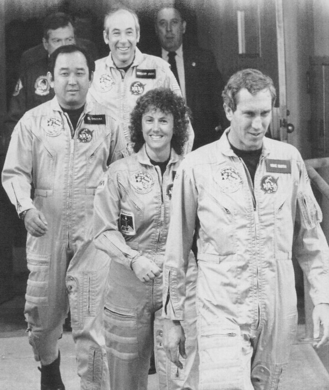 Description of . The crew of Space Shuttle 51-L walks out from their quarters en route to the Space Shuttle orbiter Challenger early Tuesday morning for a 2nd attempt at launch. Credit: AP Laserphoto