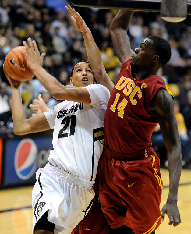 Description of . University of Colorado's Andre Roberson drives to the hoop past DeWayne Dedmon, No. 14, during a game against the University of Southern California on Thursday, Jan. 10, at the Coors Event Center on the CU campus in Boulder. Jeremy Papasso/Daily Camera