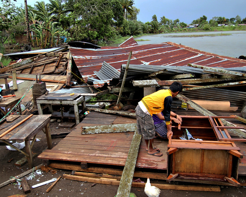 Description of . Residents prepare to assess their house which was damaged by Typhoon Bopha in Butuan city in southeastern Philippines Tuesday Dec. 4, 2012. A Philippine governor says at least 33 villagers and soldiers have drowned when torrents of water dumped by the powerful typhoon rushed down a mountain, engulfing the victims and bringing the death toll from the storm to about 40. (AP Photo/Erwin Mascarinas)