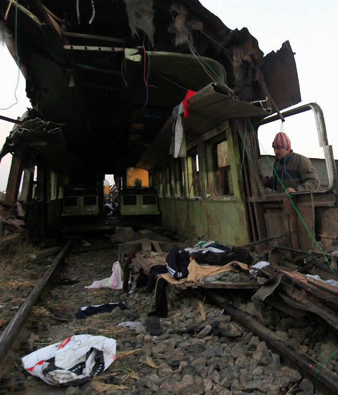 Description of . A man inspects the wreckage of a military train crash in the Giza neighbourhood of Badrashin, about 40 km (25 miles) west of Cairo, January 15, 2013. A military train carrying young recruits to an army camp derailed in a Cairo suburb on Tuesday, killing 19 people and injuring 107, Egypt's health ministry spokesman said.   REUTERS/Mohamed Abd El Ghany