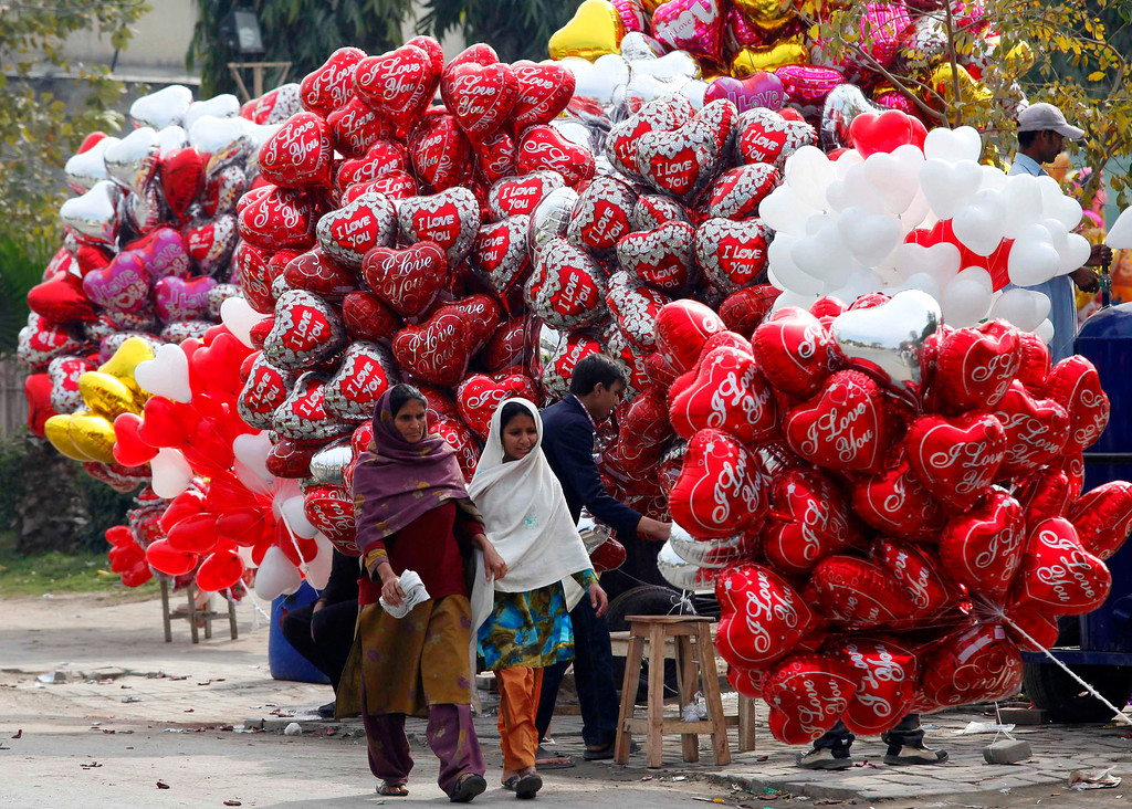 Description of . Women walk past heart-shaped balloons on Valentine's Day in Lahore, February 14, 2013. REUTERS/Mohsin Raza