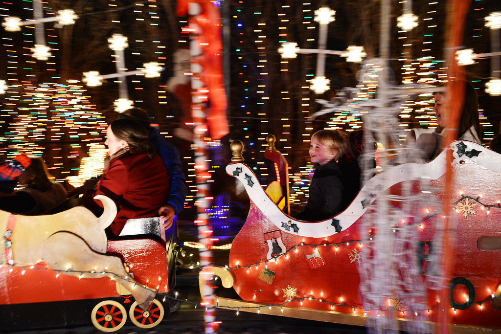 Description of . Noah Perdue (right), 4, rides Joel Occhiuzzo's annual Holiday Express Riding Train in Richardson, Texas. Occhiuzzo has operated the 46-foot-long train in his backyard for 13 years, but due to the increased insurance cost, this Christmas will likely be his last year to operate the ride. (AP Photo/The Dallas Morning News, Rose Baca)