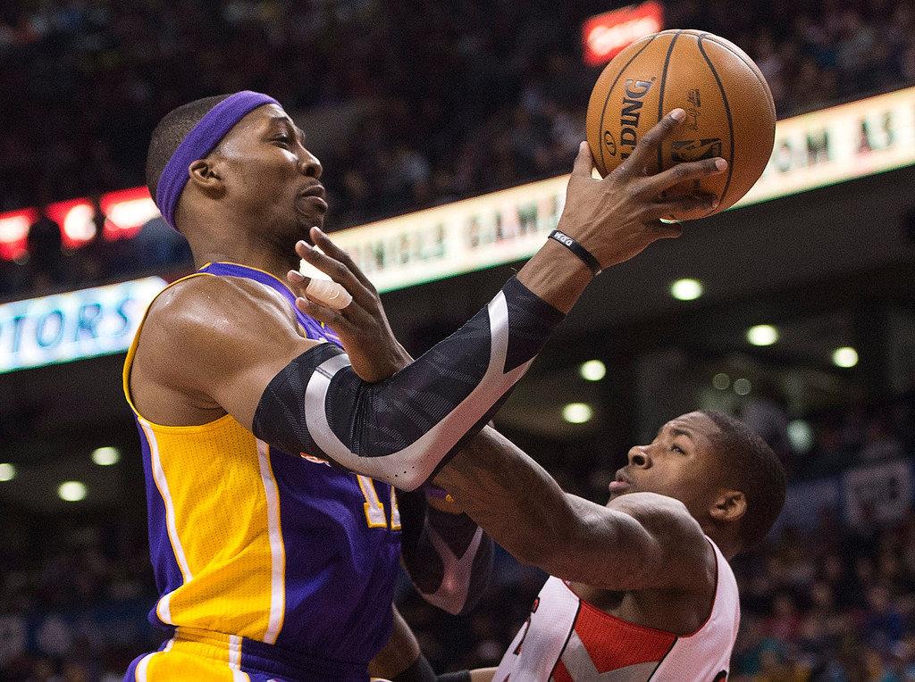 Description of . Los Angeles Lakers forward Dwight Howard, left, drives past Toronto Raptors' Ed Davis, right, during first half NBA basketball action in Toronto on Sunday Jan. 20, 2013. (AP Photo/THE CANADIAN PRESS,Nathan Denette)