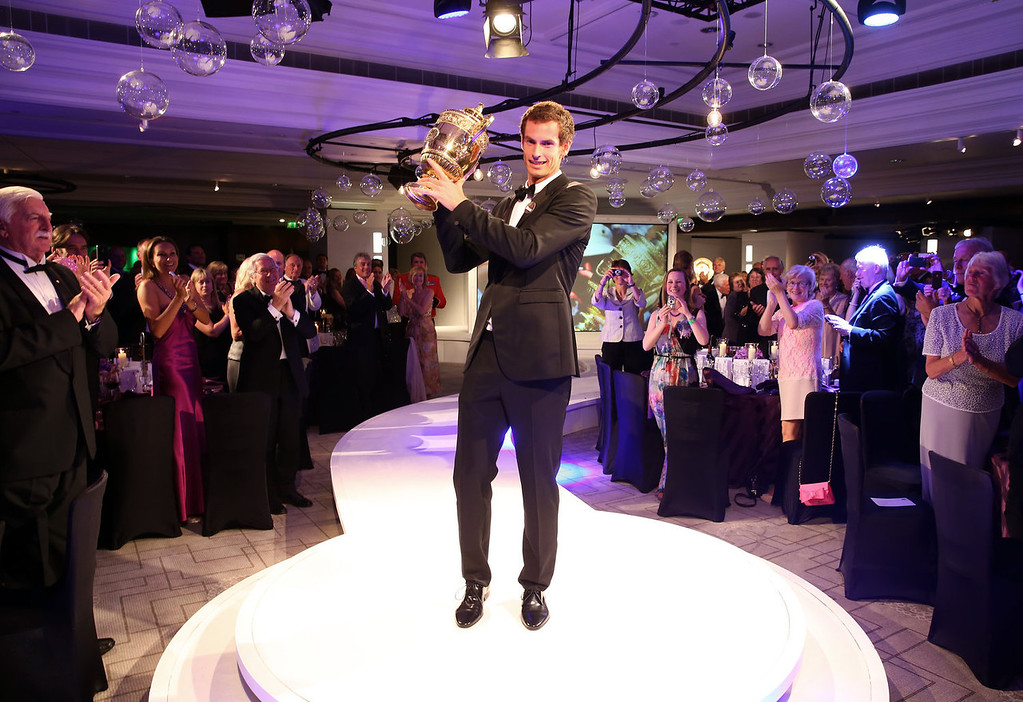 Description of . Andy Murray of Great Britain poses with the Gentlemen's Singles Trophy during the Wimbledon Championships 2013 Winners Ball at InterContinental Park Lane Hotel on July 7, 2013 in London, England.  (Photo by Julian Finney/Getty Images)