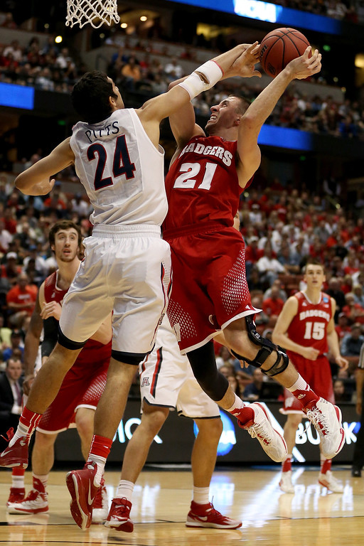 Description of . Josh Gasser #21 of the Wisconsin Badgers goes up for a shot against Elliott Pitts #24 of the Arizona Wildcats in the first half during the West Regional Final of the 2014 NCAA Men's Basketball Tournament at the Honda Center on March 29, 2014 in Anaheim, California.  (Photo by Jeff Gross/Getty Images)