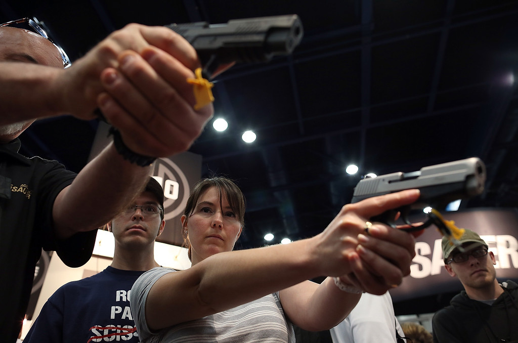 Description of . HOUSTON, TX - MAY 04:  Attendees hold handguns in the Sig Sauer booth during the 2013 NRA Annual Meeting and Exhibits at the George R. Brown Convention Center on May 4, 2013 in Houston, Texas.  More than 70,000 peope are expected to attend the NRA's 3-day annual meeting that features nearly 550 exhibitors, gun trade show and a political rally. The Show runs from May 3-5.  (Photo by Justin Sullivan/Getty Images)
