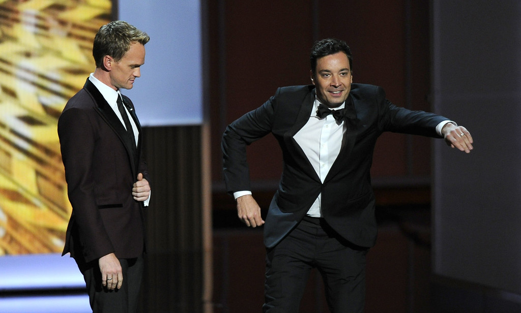 Description of . Host Neil Patrick Harris, left, and Jimmy Fallon speak on stage at the 65th Primetime Emmy Awards at Nokia Theatre on Sunday Sept. 22, 2013, in Los Angeles.  (Photo by Chris Pizzello/Invision/AP)