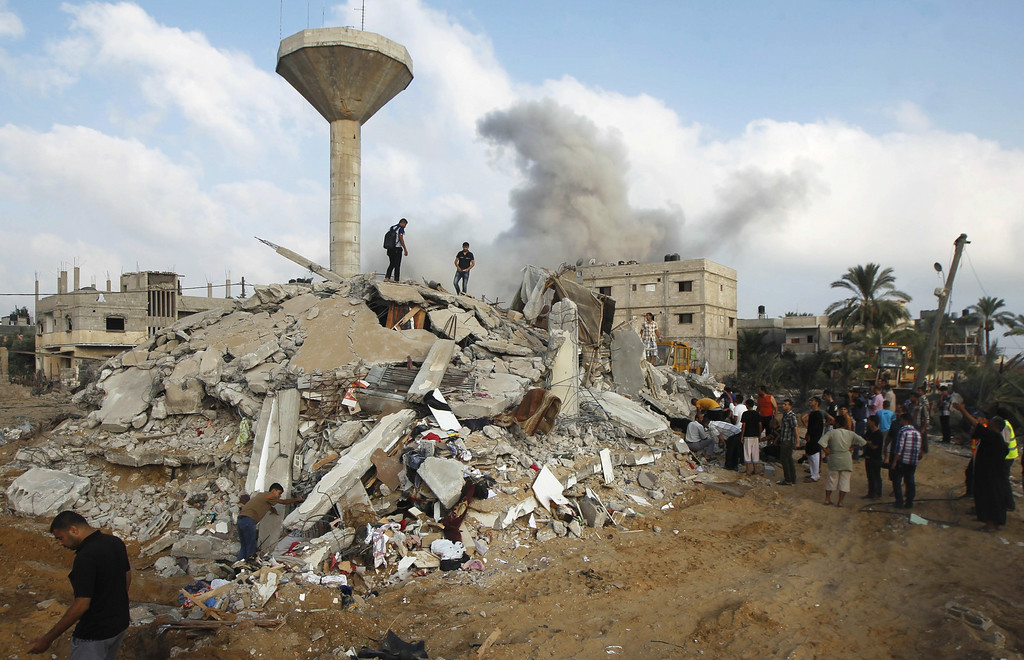 Description of . Smoke rises while Palestinian rescuers search for victims under the rubble of the home of the  Duheir family, after it was destroyed by an Israeli air strike in Rafah on July 29, 2014, in the southern of Gaza strip.   AFP PHOTO/ SAID  KHATIB/AFP/Getty Images