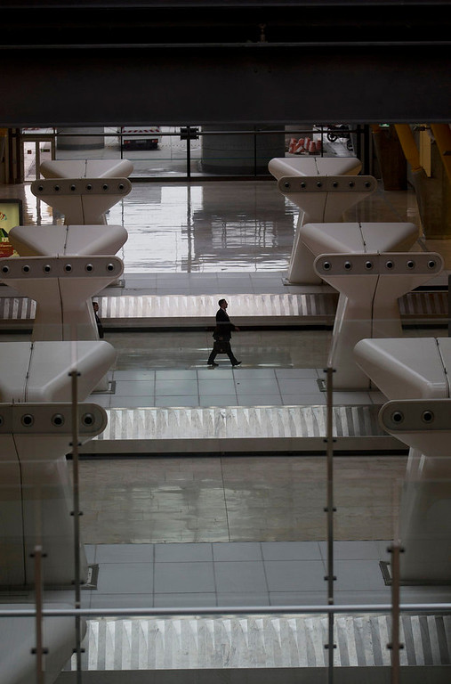 . A man walks past empty baggage conveyors at Barajas international airport in Madrid, Spain Monday Feb. 18, 2013. Workers at Iberia airlines begin the first of 15 days of strikes to protest the company\'s plan to cut almost a fifth of its workforce. The pilots union is yet to decide if it will join the stoppage. International Airlines Group, which includes British Airways and Iberia, has said the Spanish airline is fighting to survive. (AP Photo/Paul White)