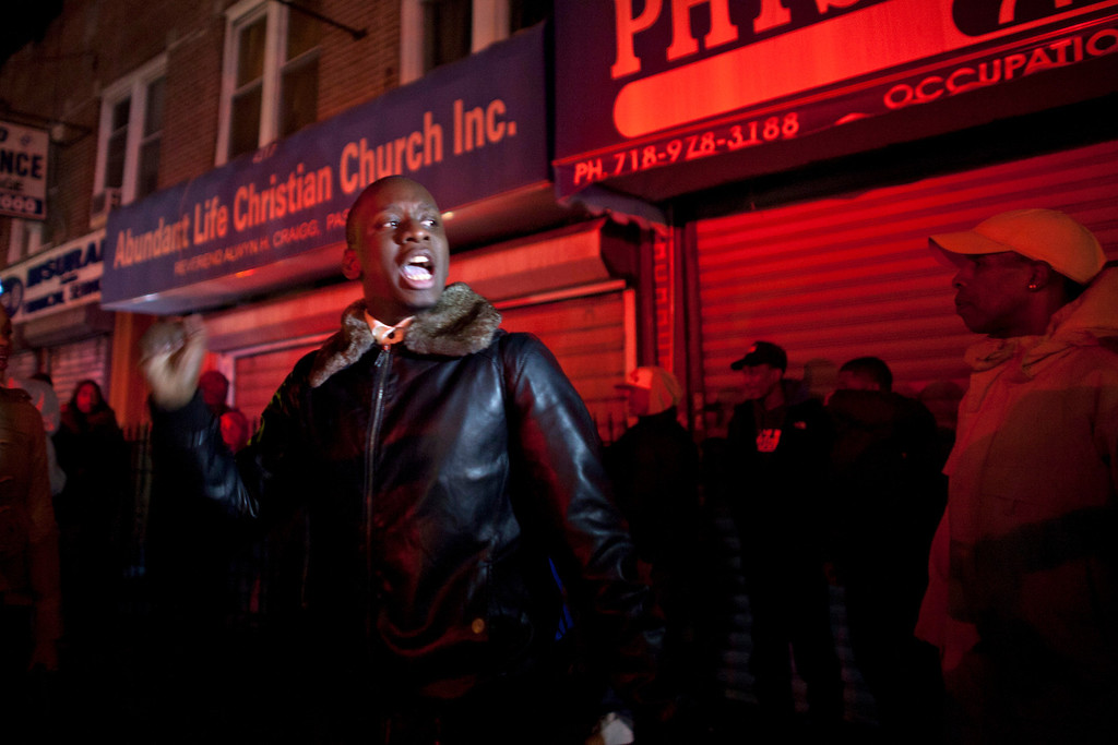 Description of . A youth shouts slogans against New York Police Department (NYPD) officers during a protest against the killing of 16-year-old Kimani