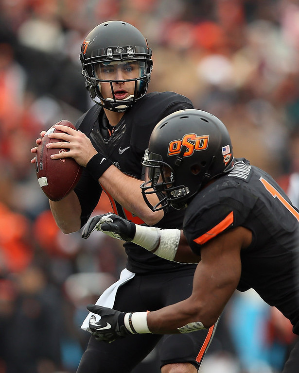 Description of . Clint Chelf #10 of the Oklahoma State Cowboys passes against the Purdue Boilermakers during the Heart of Dallas Bowl at Cotton Bowl on January 1, 2013 in Dallas, Texas.  (Photo by Ronald Martinez/Getty Images)