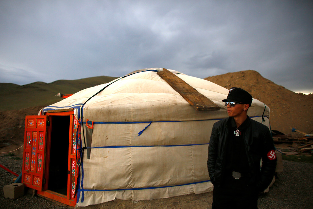 Description of . A member of the Mongolian neo-Nazi group Tsagaan Khass stands next to a 'ger', a traditional Mongolian tent, at a quarry, where they questioned a worker, southwest of Ulan Bator June 23, 2013. The group has rebranded itself as an environmentalist organisation fighting pollution by foreign-owned mines, seeking legitimacy as it sends Swastika-wearing members to check mining permits. Over the past years, ultra-nationalist groups have expanded in the country and among those garnering attention is Tsagaan Khass, which has recently shifted its focus from activities such as attacks on women it accuses of consorting with foreign men to environmental issues, with the stated goal of protecting Mongolia from foreign mining interests. This ultra-nationalist group was founded in the 1990s and currently has 100-plus members. Picture taken June 23, 2013.   REUTERS/Carlos Barria