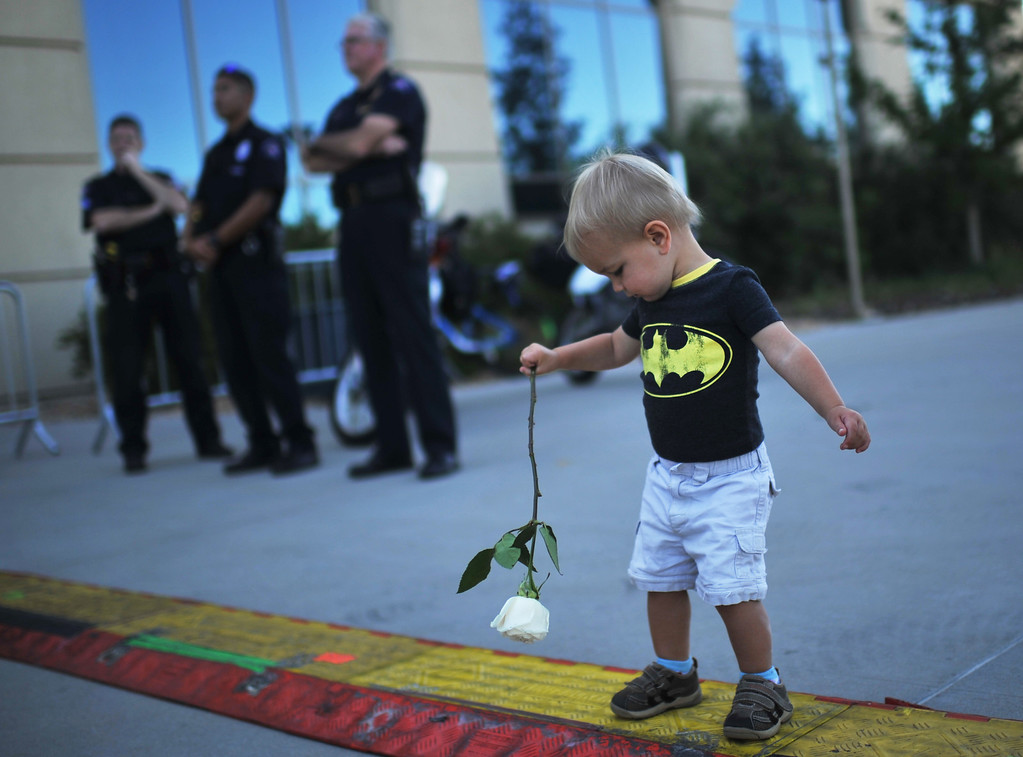 Description of . AURORA, CO. - July 20: Reeve Mooney, age 1, holds a rose during a day of remembrance at the Aurora Municipal Center. Aurora, Colorado. July 20, 2013. People gathered outside the Aurora Municipal Center to mark the first anniversary of the deaths of 12 people and the injury of at least 70 others in a mass shooting that forever changed an entire community. (Photo By Hyoung Chang/The Denver Post)