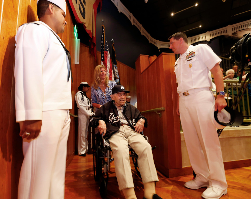 Description of . Baseball Hall of Famer Yogi Berra enters, as he is honored by the U.S. Navy for his service 70 years ago during the D-Day Invasion, at a ceremony at the Yogi Berra Museum in Montclair, N.J.  on Friday, June 6, 2014. (AP Photo/Rich Schultz)