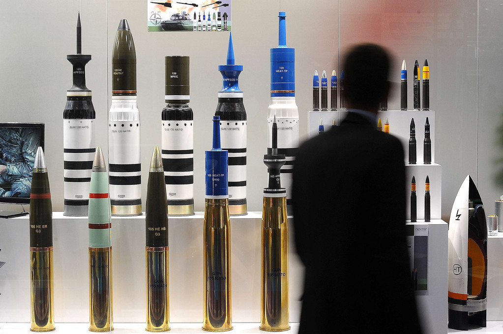 Description of . A man looks at tank ammunition at the Defence and Security Equipment International (DSEI) arms fair at the ExCeL centre in east London, on September 10, 2013.  AFP PHOTO / BEN STANSALL/AFP/Getty Images