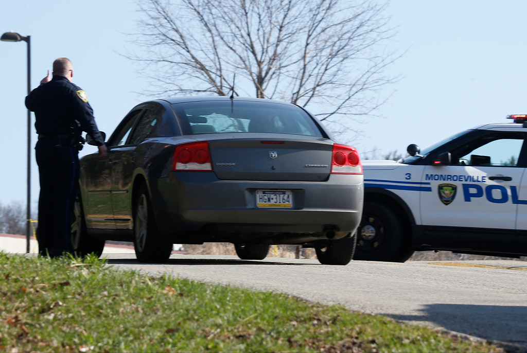 Description of . A policeman directs a driver to the area to pick up students on the campus of the Franklin Regional School District where several people were stabbed at Franklin Regional High School on Wednesday, April 9, 2014, in Murrysville, Pa., near Pittsburgh. The suspect, a male student, was taken into custody and being questioned. (AP Photo/Keith Srakocic)