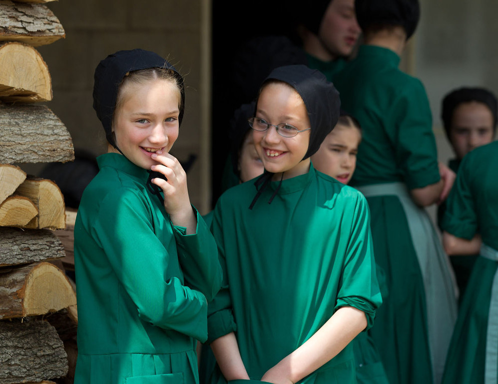 Description of . Amish girls gather outside the school house prior to the start of their final day of class in Bergholz, Ohio on Tuesday, April 9, 2013. (AP Photo/Scott R. Galvin)