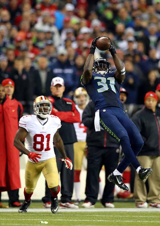 . Strong safety Kam Chancellor #31 of the Seattle Seahawks makes an interception in the fourth quarter in front of wide receiver Anquan Boldin #81 of the San Francisco 49ers during the 2014 NFC Championship at CenturyLink Field on January 19, 2014 in Seattle, Washington.  (Photo by Ronald Martinez/Getty Images)