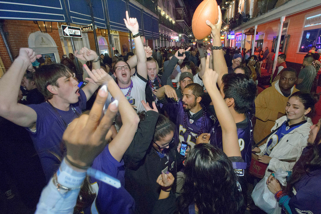 Description of . Baltimore Ravens fans celebrate the team's victory as fans from the Ravens and San Francisco 49ers NFL football teams pack the French Quarter on Bourbon Street for Super Bowl XLVII near the Royal Sonesta Hotel in New Orleans, Sunday, Feb. 3, 2013. (AP Photo/Matthew Hinton)
