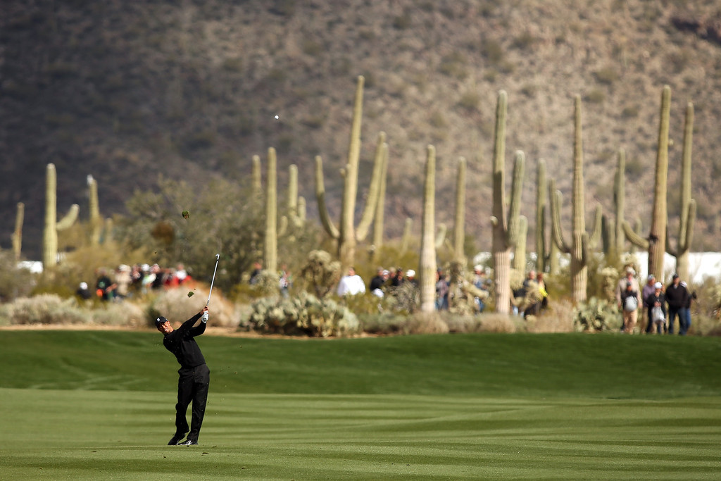 Description of . MARANA, AZ - FEBRUARY 21:  Tiger Woods hits a shot from the fairway on the first hole during the first round of the World Golf Championships - Accenture Match Play at the Golf Club at Dove Mountain on February 21, 2013 in Marana, Arizona. Round one play was suspended on February 20 due to inclimate weather and is scheduled to be continued today.  (Photo by Darren Carroll/Getty Images)